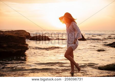 Full length side view image of young brunette woman in light summer dress walking near the sea on sunset