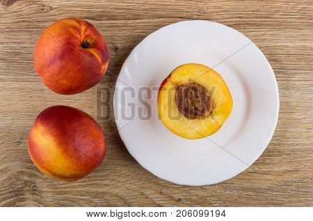 Nectarines And Half Of Nectarine In Plate On Wooden Table