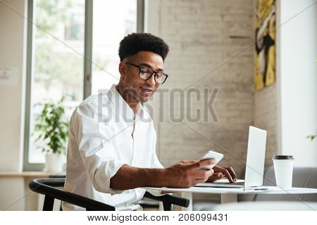 Photo of handsome young african man sitting coworking with laptop computer. Looking aside chatting by phone.