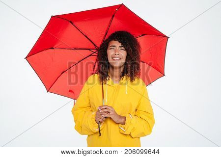 Tired african woman in raincoat crying while hiding under umbrella over white background