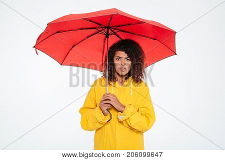 Confused african woman in raincoat hiding under umbrella and looking at the camera over white background