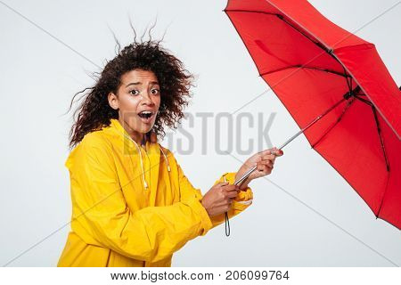 Side view of confused surprised african woman in raincoat holding umbrella and looking at the camera over white background