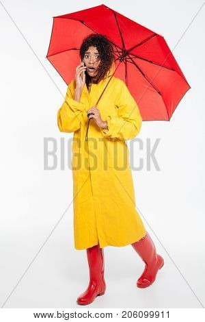Full length image of confused african woman in raincoat walking with umbrella and talking by the smartphone while looking at the camera over white background