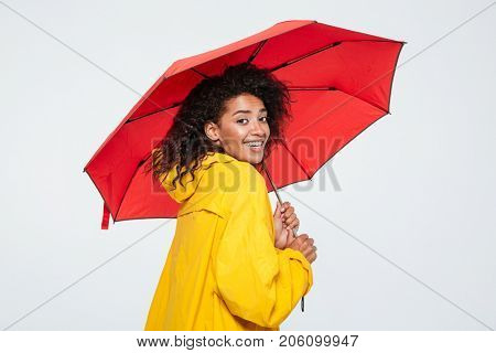 Back view of smiling african woman in raincoat hiding under umbrella nd looking at the camera over white background