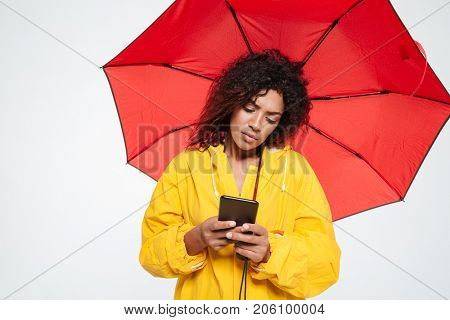 Calm african woman in raincoat hiding under umbrella and writing message on her smartphone over white background