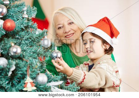 Grandchild helping his grandmother to decorate the christmas tree at home