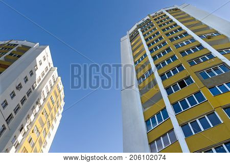 Two new multi-storey houses painted in yellow and blue on the sky.