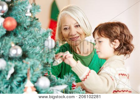 Grandmother decorating christmas tree together with her grandchild