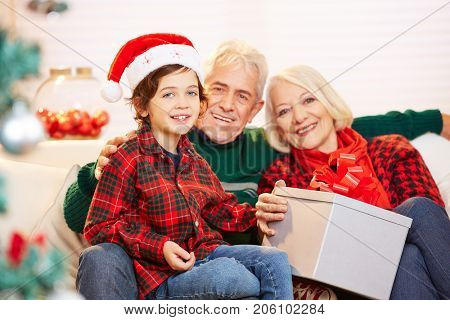 Grandchild and grandparents celebrating christmas together with a big gift