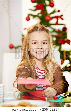 Happy girl giving wishlist with her wishes for christmas