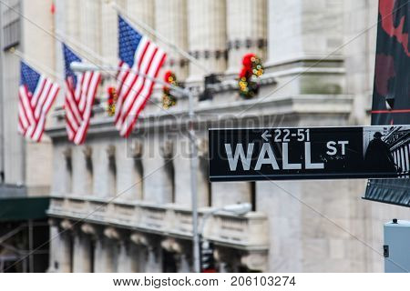 NEW YORK, NY - NOVEMBER  28: Wall Street  sign with american flag  and with New York Stock Exchange USA seen in November 28, 2016 in New York City