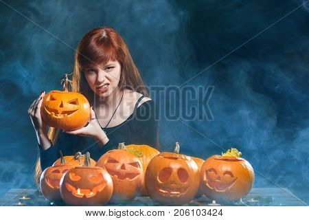 Red haired woman with Halloween pumpkins over smoky background showing her wild side growling at you