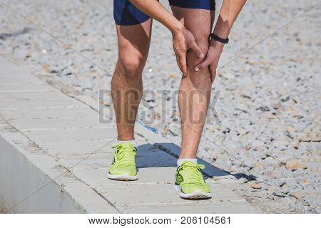 Running athlete feeling pain after having his knee injured. Accident on running track during the morning exercise. Sport accident concepts