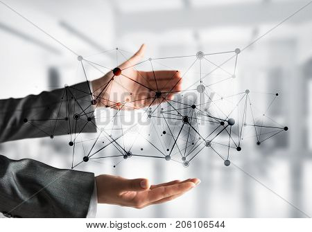 Business woman in suit keeping black social media network structure in hands with office view on background. Mixed media.