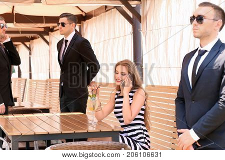 Young businesswoman with bodyguards in cafe