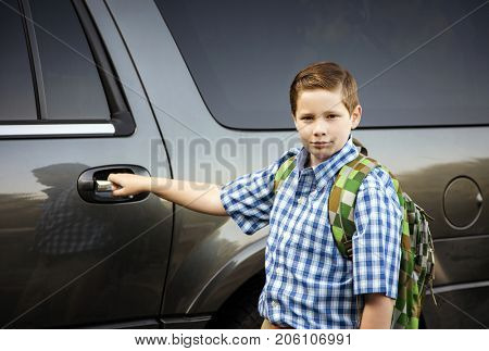 Young schoolboy getting into a car