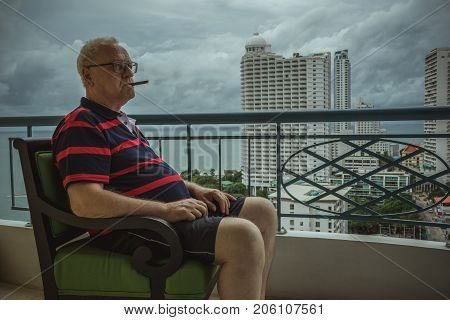 An elderly man is smoking a cigar while sitting on the balcony and watching the rainy weather. Gloomy sky, rainy day