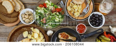 Outdoors Food Concept. Appetizing Barbecued Chicken Legs, Chips And A Salad Of Fresh Vegetables On A
