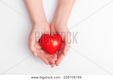 People, relationship and love concept - close up of womans cupped hands showing red heart