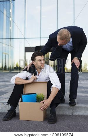 Fired business man sitting frustrated and upset on the street near office building with box of his belongings. He lost work. Other businessman comforts and encourages him