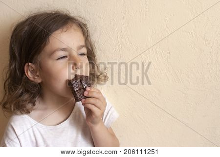 The girl inhales the favorite smell of her milk chocolate