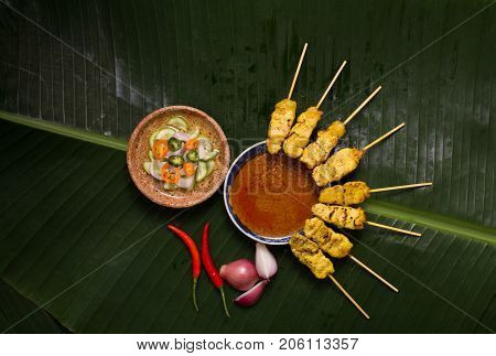 Pork satay skewer with peanut sauce decorated with cucumber sauce, onion, chili on banana leaf.