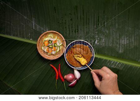 A hand having pork satay dipping peanut sauce decorated with cucumber sauce, onion, chili on banana leaf.