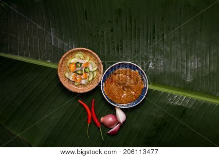 Satay peanut and cucumber sweet and sour sauces on banana leaf decorated with shallot and red Thai chili with copy space.