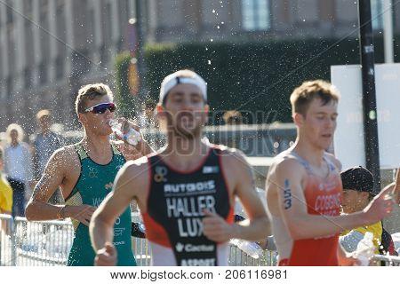 STOCKHOLM - AUG 26 2017: Running triathlete Marcel Walkington (AUS) splashing water from a bottle over his body defocused competitors in the Men's ITU World Triathlon series event August 26 2017 in Stockholm Sweden