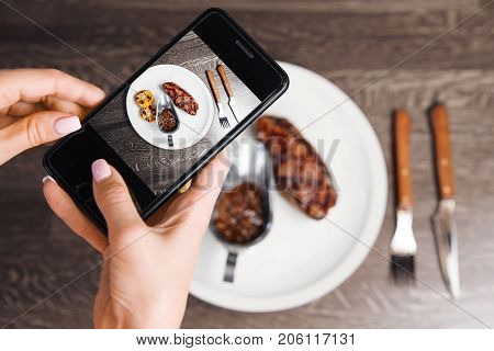 Photo on smartphone of beefsteak with grilled corn and sauce in iron bowl on white plate, closeup view on just prepared dish with meat and vegetables