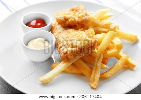Plate with tasty fried fish, chips and sauces on table, closeup