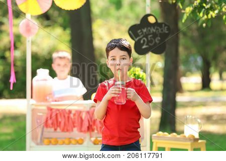 Adorable little boy with jar of homemade lemonade in park