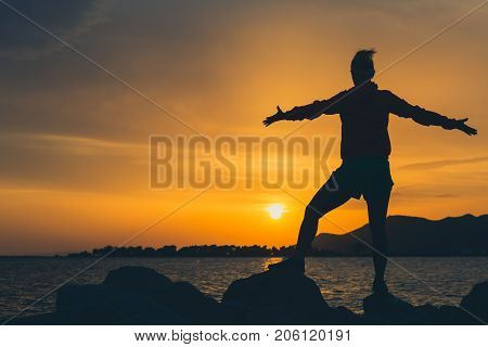 Woman with arms outstretched at a seaside. Beautiful inspiring landscape and sea with girl and hands raised on sunset Croatia.