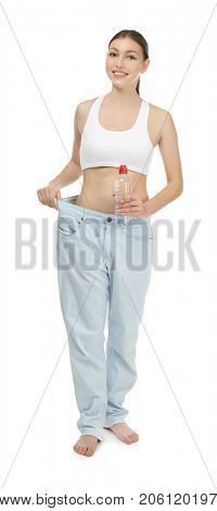 Beautiful young woman in oversized jeans with bottle of water on white background. Diet concept