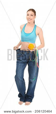 Beautiful young woman in oversized jeans with orange and measuring tape on white background. Diet concept