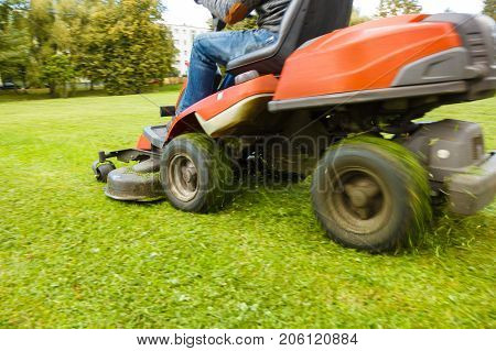the lawn mower drives through a green meadow