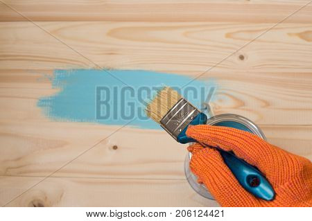 the employee paints the a wooden table. worker paints wooden board. brush in hand. hand in gloves. House renovation, paint can on the old wooden background with copy space