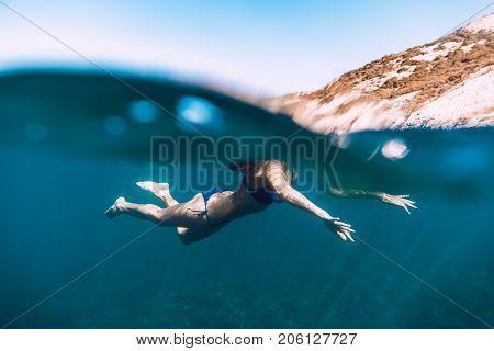Woman swimming in ocean, underwater photo. Blue ocean in Bali