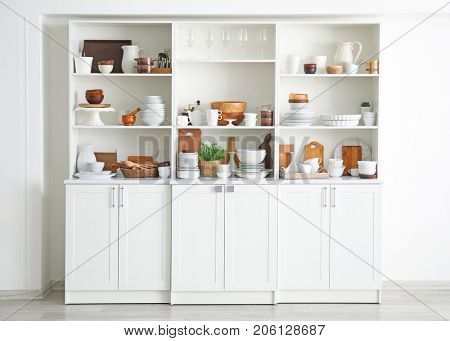 White storage stand with ceramic and wooden dishware in kitchen