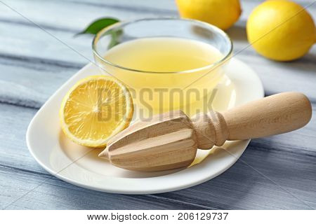Composition with fresh lemon juice and squeezer on wooden background