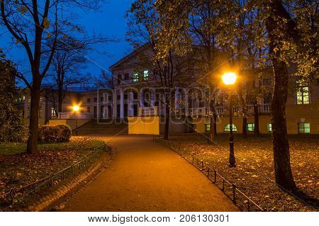 Night view of park footpath and building of State University of Communication in Yusupov Garden Saint Petersburg Russia