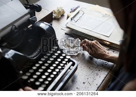 Closeup of vintage retro typewriting with hand and cigarette ashtray