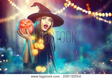 Halloween Witch with a carved Pumpkin and magic lights in a dark forest. Beautiful young surprised woman in witches hat and costume holding pumpkin. Halloween party art design