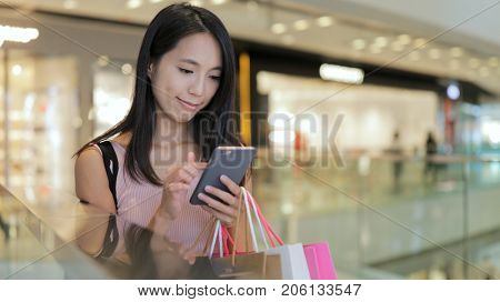Woman use of smart phone and holding shopping bags