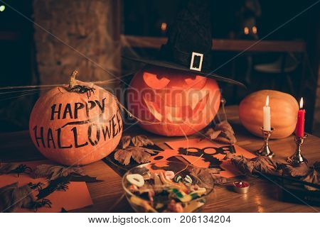 Close Up Of Cutted Pumpkin, Fall Leaves, Spider Web Net, Skull, Cap Of Witch, Bowl With Candies On T