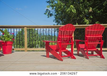 View of 2 empty red muskoka chairs on a wood deck, ready to enjoy the view in the canadian summer