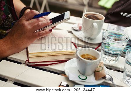 Woman's hands with cell phone and pen two cups of coffee meeting for two.