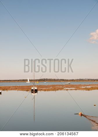 Boat Moored In Estuary Scene With Mast Reflected In Water Blue Sky