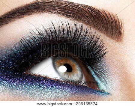 woman's eye with blue eye makeup
