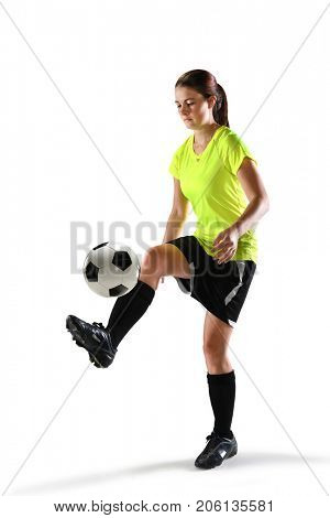 Young female soccer player balancing ball isolated over white background